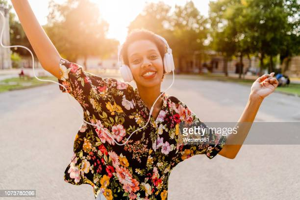 happy fashionable young woman with headphones dancing outdoors at sunset - solo una donna giovane foto e immagini stock