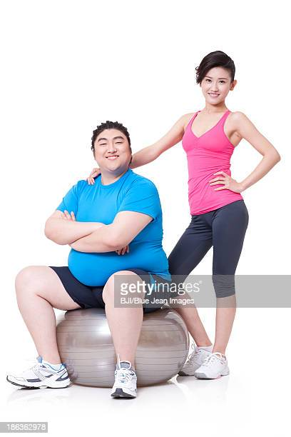 Happy fat man and girlfriend with fitness ball
