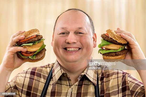 Happy fat man holding two hamburgers and looking at camera.