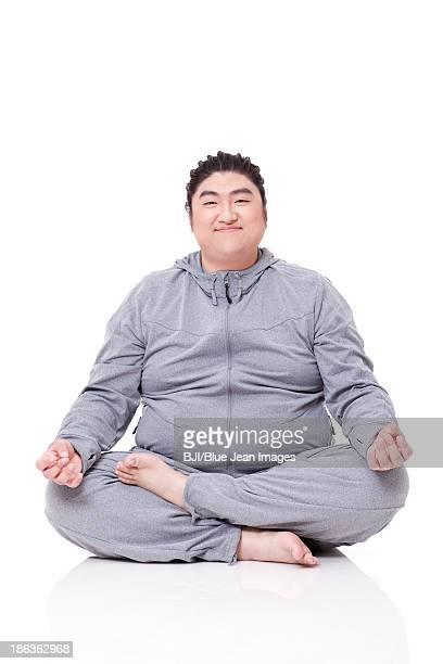 Happy fat man sitting cross-legged