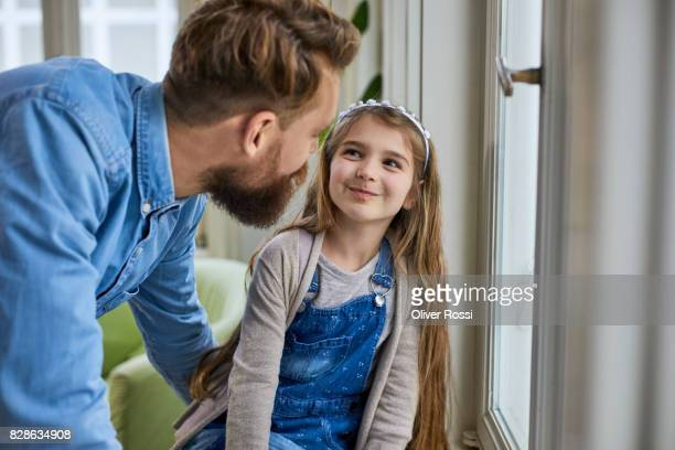 Happy father and daughter at the window