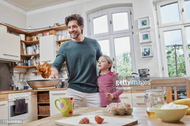 happy father and daughter baking pancakes in kitchen at home together - pancakes stock pictures, royalty-free photos & images