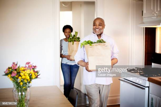 Happy father and daughter carrying paper bags with food at home