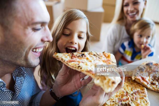 happy father and daughter eating pizza for lunch after moving into new home. - pizza stock pictures, royalty-free photos & images