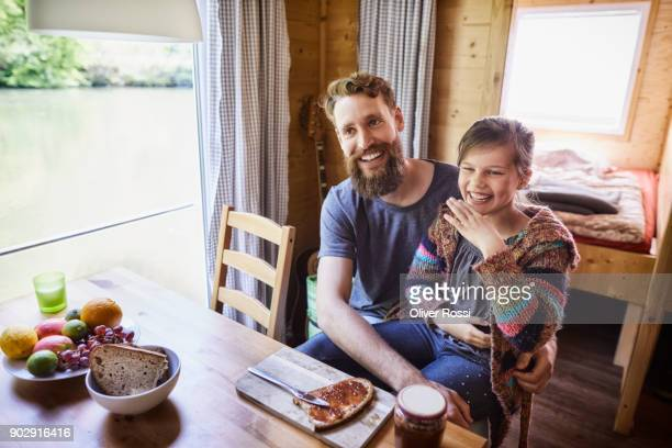 Happy father and daughter having breakfast on a houseboat