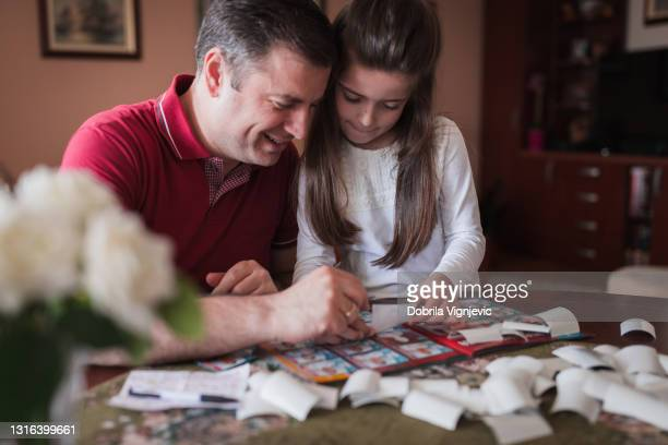 happy father and daughter having fun with football player stickers and the album - final game stock pictures, royalty-free photos & images