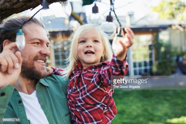 happy father and daughter in backyard - wirkliches leben stock-fotos und bilder