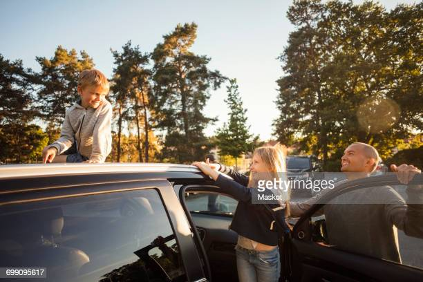 Happy father and daughter looking at boy sitting on car roof