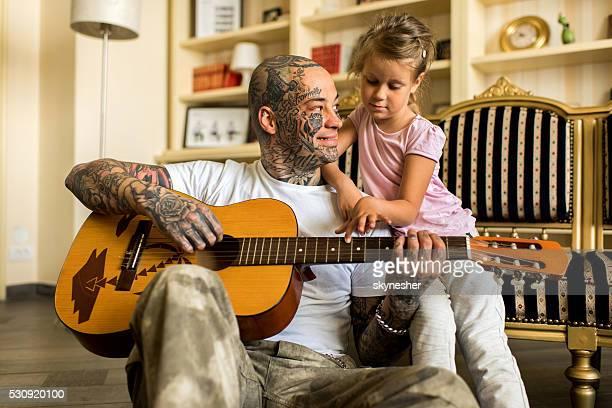 Glückliche Vater und Tochter spielen Akustikgitarre wie zu Hause fühlen.