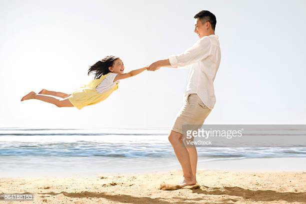 Happy father and daughter playing on the beach