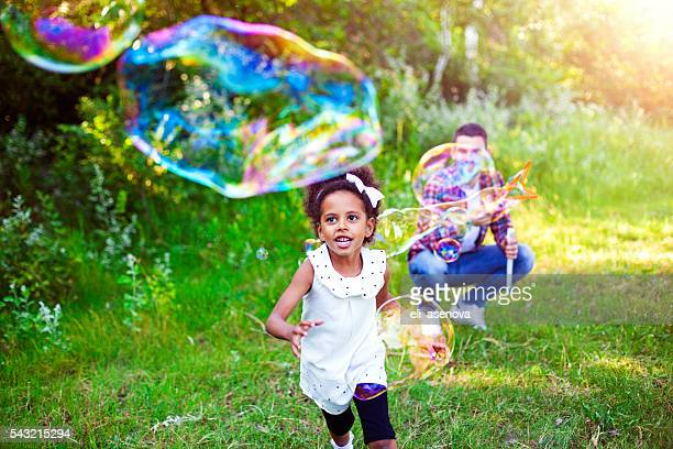 Happy father and daughter playing soap bubbles in park.