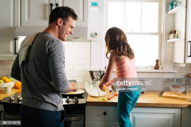 Happy father and daughter preparing food in kitchen at home