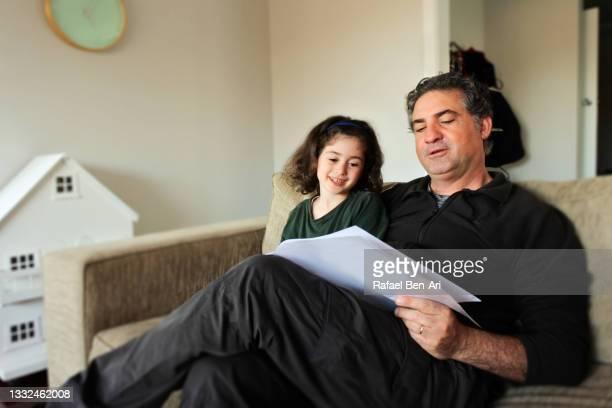 happy father and daughter reading a book together - rafael ben ari fotografías e imágenes de stock