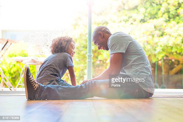 Happy father and daughter sitting on floor at home