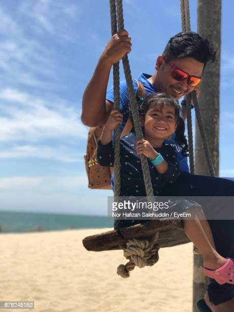 Happy Father And Daughter Swinging At Beach