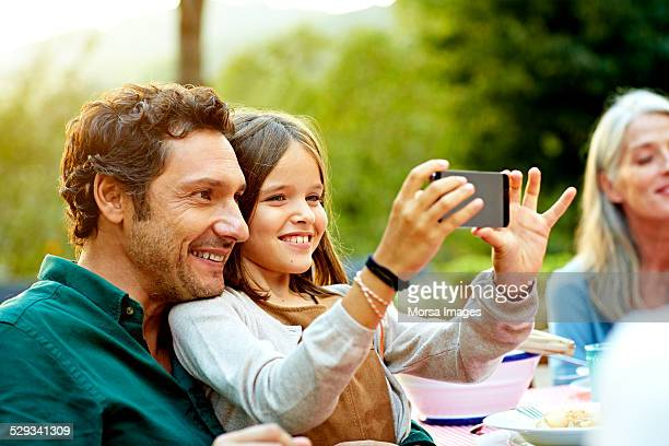 Happy father and daughter taking selfie in yard