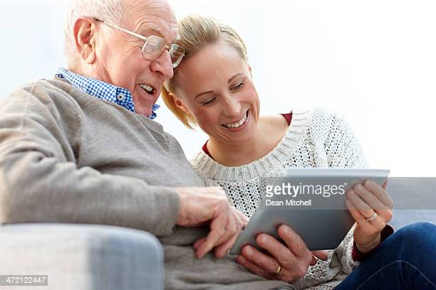 Happy father and daughter using digital tablet at home