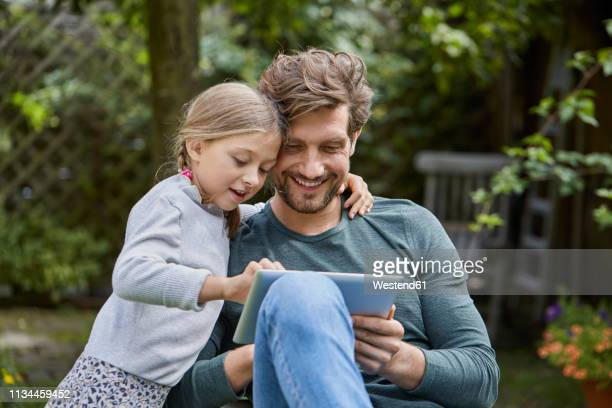 happy father and daughter using tablet together in garden - explaining stock pictures, royalty-free photos & images