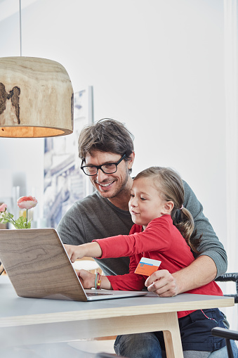 Happy father and daughter with a card using laptop on table at home - gettyimageskorea