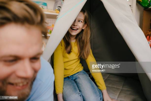 happy father and daughter with teepee in children's room - kind im grundschulalter stock-fotos und bilder