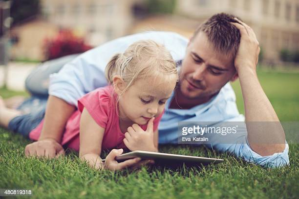 Happy father and his daughter using digital tablet outdoors