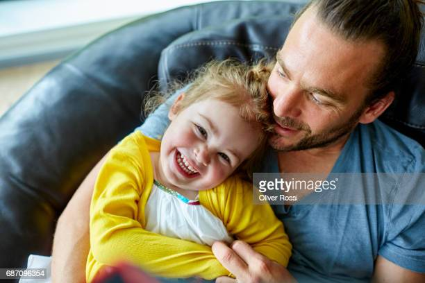 Happy father and little daughter on the couch