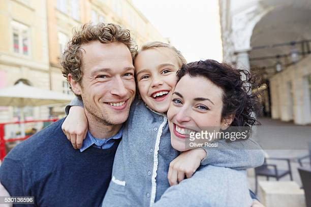 happy father and mother with daughter outdoors - junge familie stock-fotos und bilder