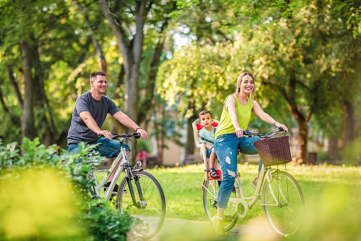 Happy father and mother with kid on bicycles having fun in park. 1147373940