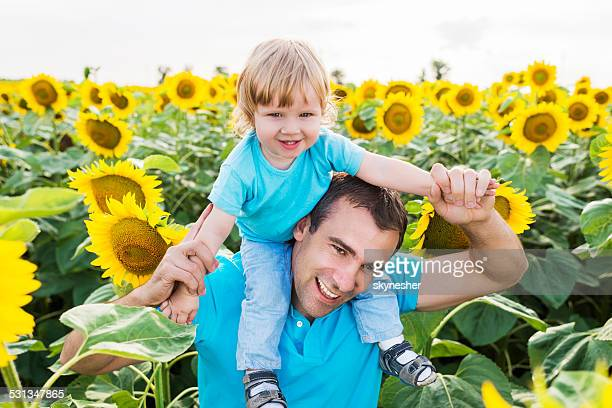 Happy father and son among sunflowers.