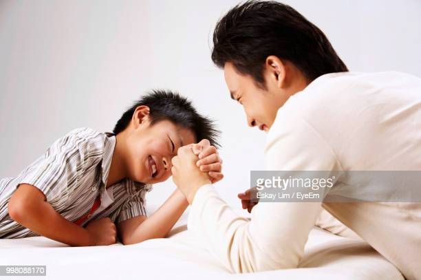 Happy Father And Son Arm Wrestling On Mattress Against White Background