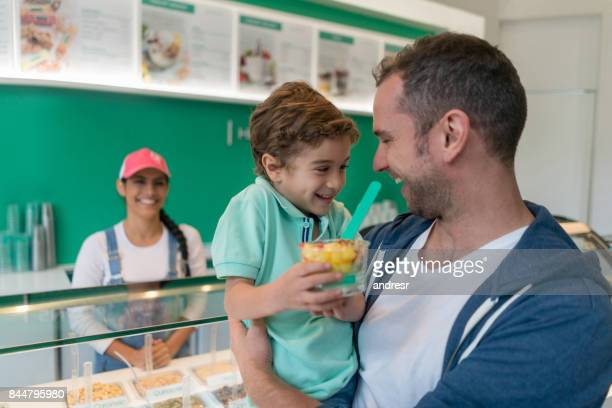 happy father and son at the ice cream shop - ice cream parlour stock pictures, royalty-free photos & images