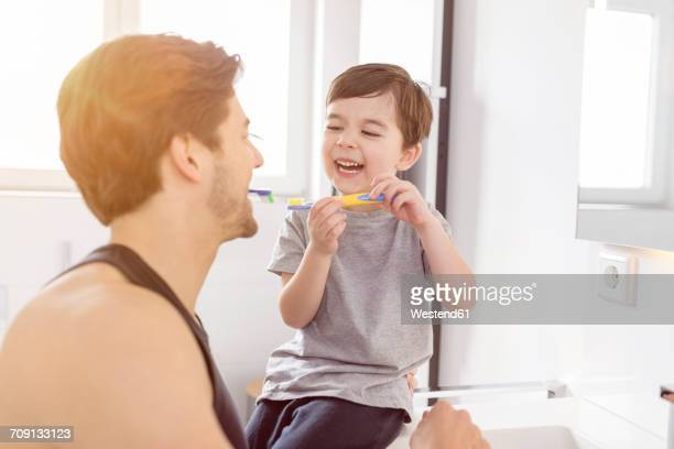 Happy father and son brushing teeth together in bathroom