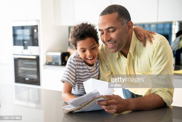happy father and son checking their mail at home - mail stock pictures, royalty-free photos & images