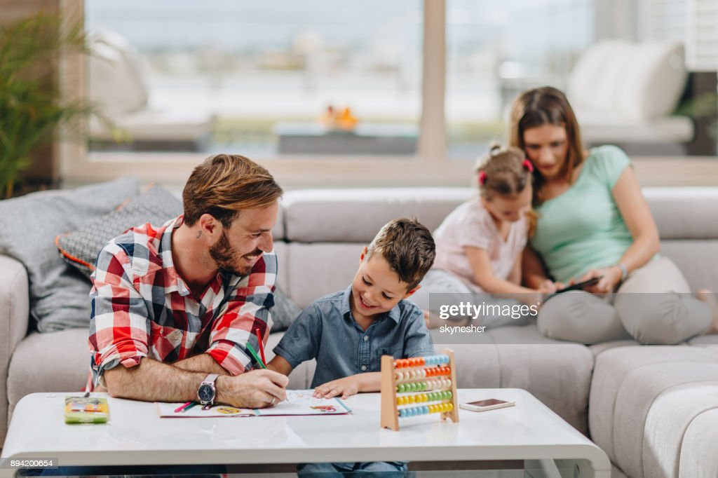Happy father and son coloring on the paper in the living room. : Stock Photo