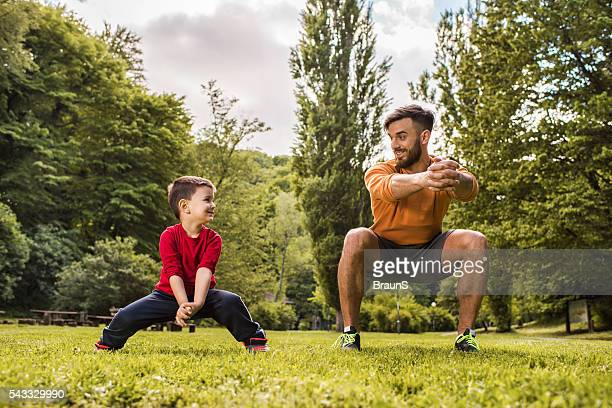 Happy father and son doing strength exercises in nature.