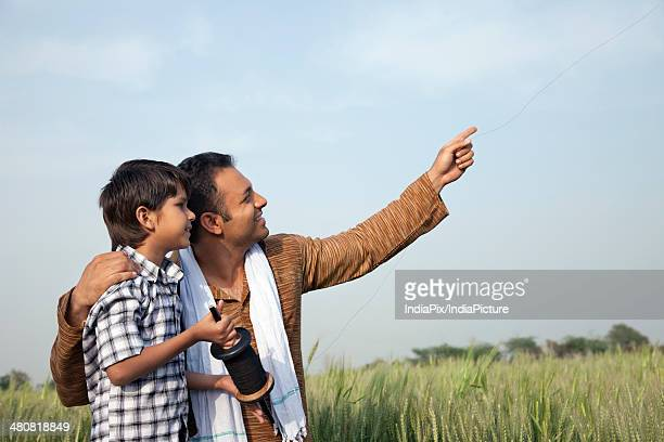 Happy father and son flying a kite in field against sky