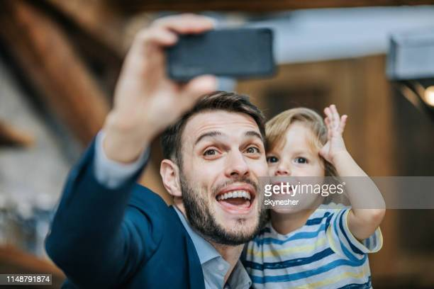 happy father and son making faces while taking a selfie with cell phone. - photo messaging stock pictures, royalty-free photos & images