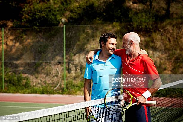 Happy father and son on tennis court
