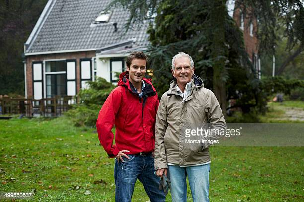Happy father and son outside cottage