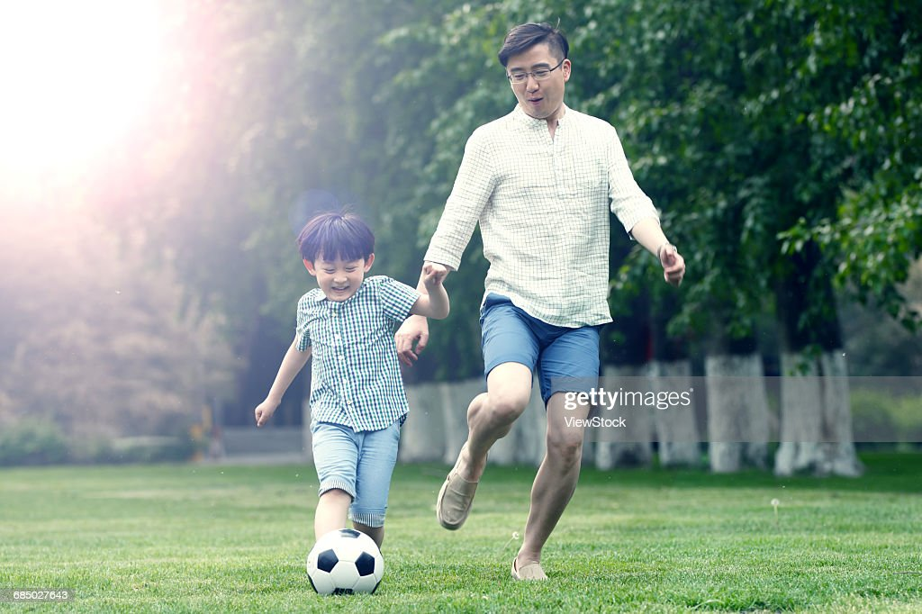 Happy father and son play football on the grass : Stock Photo