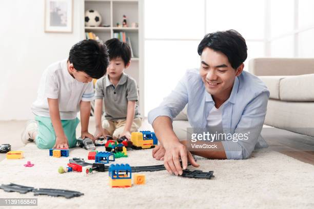 happy father and son play in the living room - china east asia stock-fotos und bilder