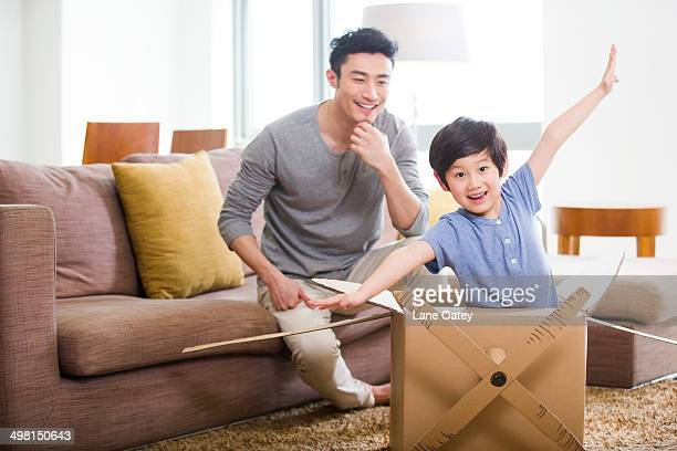 Happy father and son playing cardboard airplane