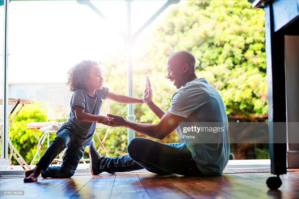 Happy father and son playing on floor at home : Stock Photo