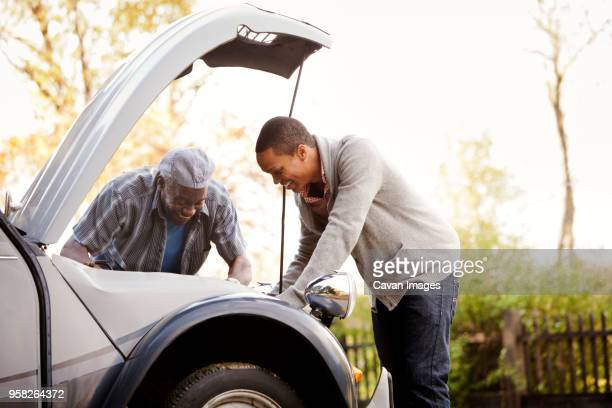 Happy father and son repairing car against sky