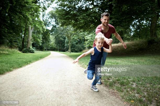 happy father and son running on a path in a park - carefree stock pictures, royalty-free photos & images