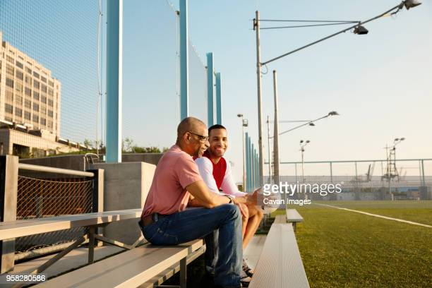 happy father and son sitting on bleachers at soccer field - old american football stock photos and pictures