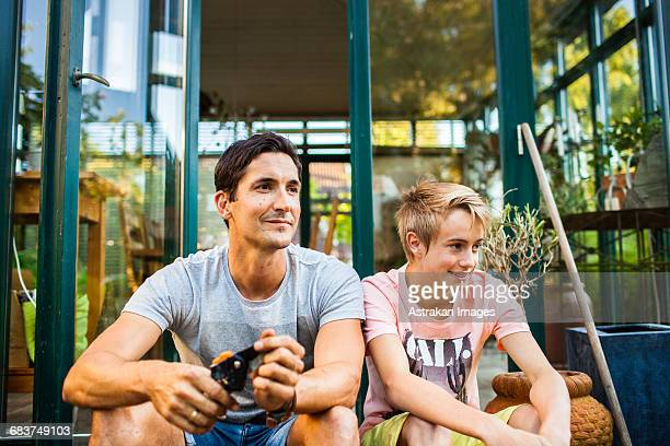 Happy father and son sitting outside house