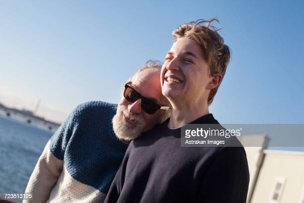 Happy father and son standing against clear blue sky