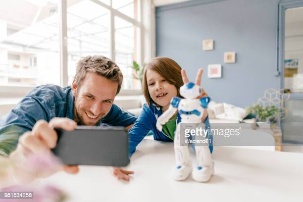 happy father and son taking a selfie with robot on table at home - één ouder stockfoto's en -beelden