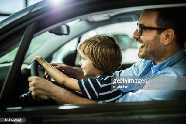 happy father and son testing new car in a showroom. - test drive stock pictures, royalty-free photos & images